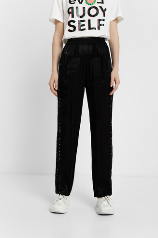 Trousers in glossy logomania
